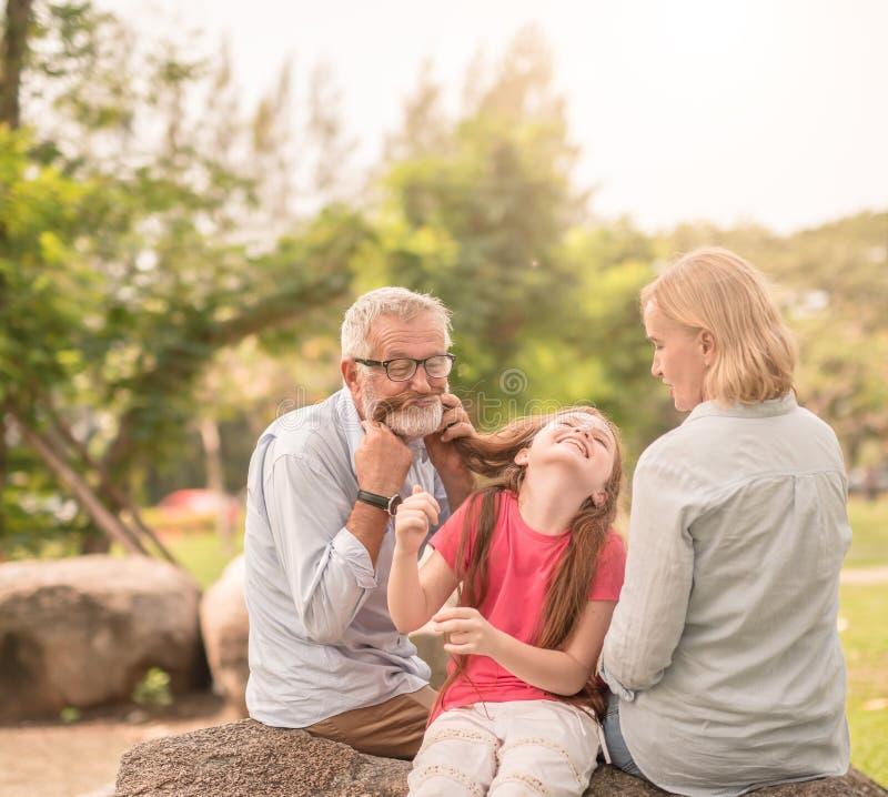 Família feliz que joga no parque do jardim fotos de stock royalty free