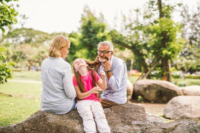 Família feliz que joga no parque do jardim imagens de stock