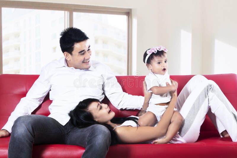 Família feliz que joga no sofá fotos de stock