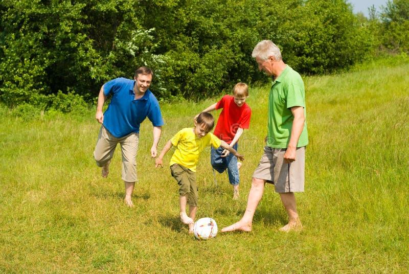 Família feliz que joga o futebol fotografia de stock