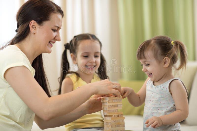 Família feliz que joga o jenga junto em casa Mamã e filhas que têm o divertimento na sala de visitas imagem de stock