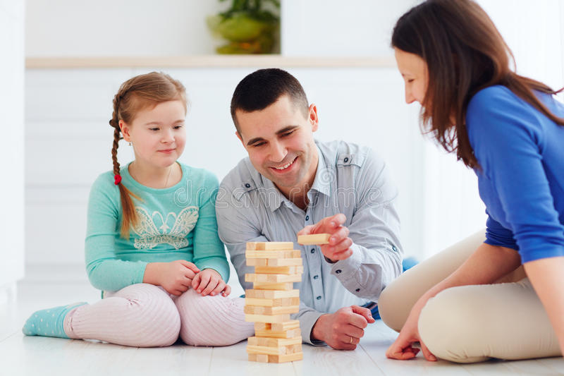Família feliz que joga o jogo do jenga em casa imagem de stock royalty free