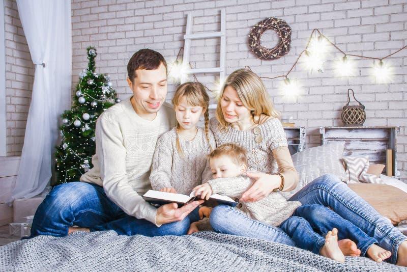 Família feliz que lê um livro em casa no Natal fotografia de stock royalty free
