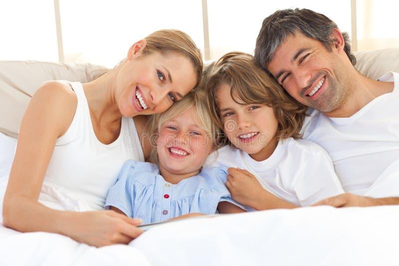 Família feliz que lê um livro na cama fotos de stock royalty free