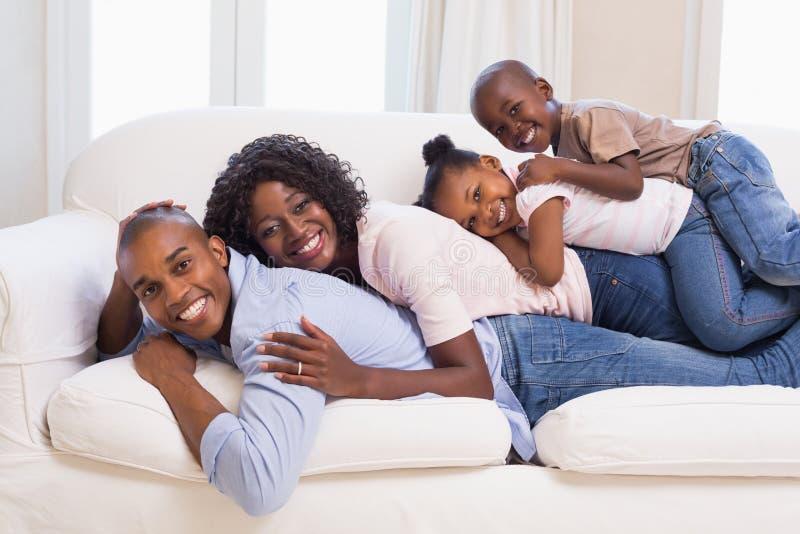 Família feliz que levanta no sofá junto imagem de stock
