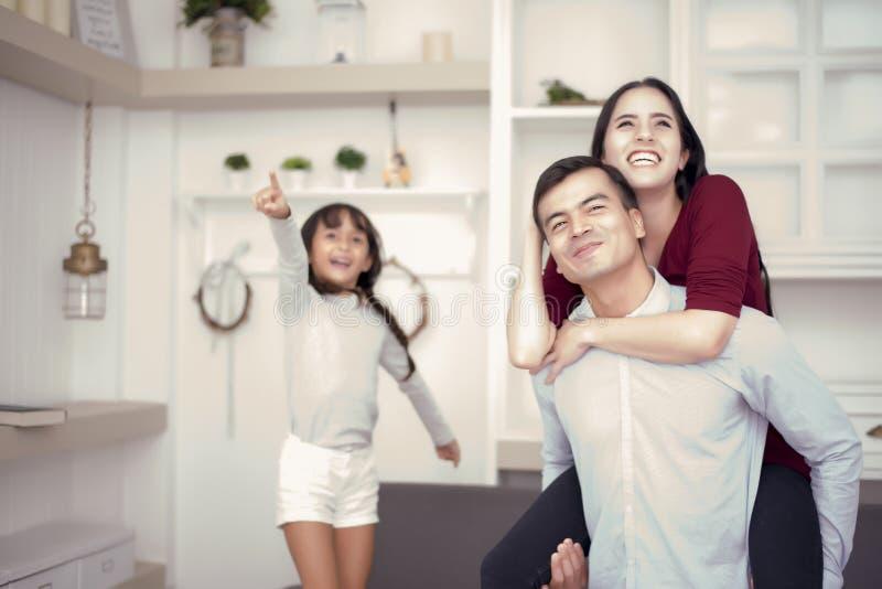 Família feliz que olha a parte externa com humores felizes, a parte traseira do passeio da mamã no paizinho, menina que aponta à  fotografia de stock