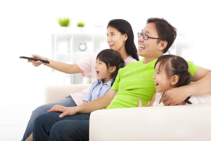 Família feliz que olha a tevê fotografia de stock royalty free