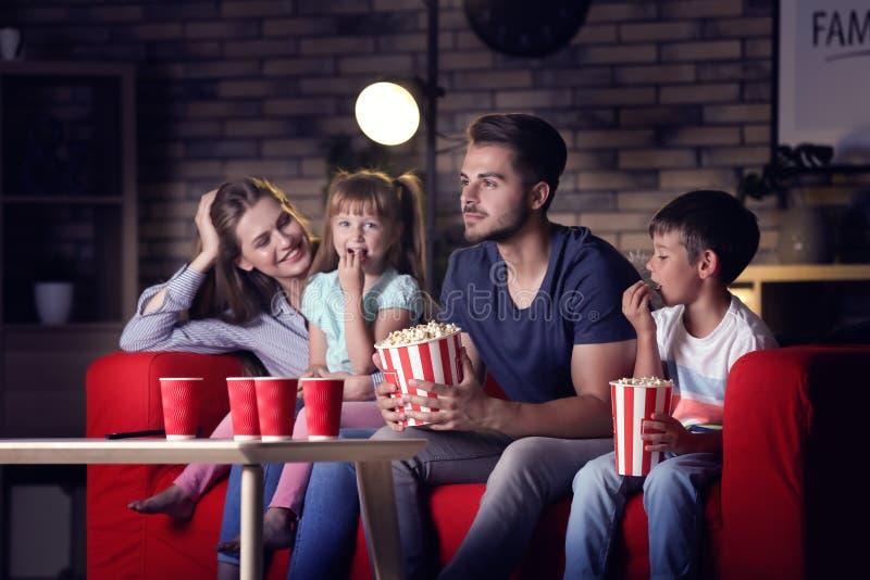 Família feliz que olha a tevê no sofá na noite imagem de stock