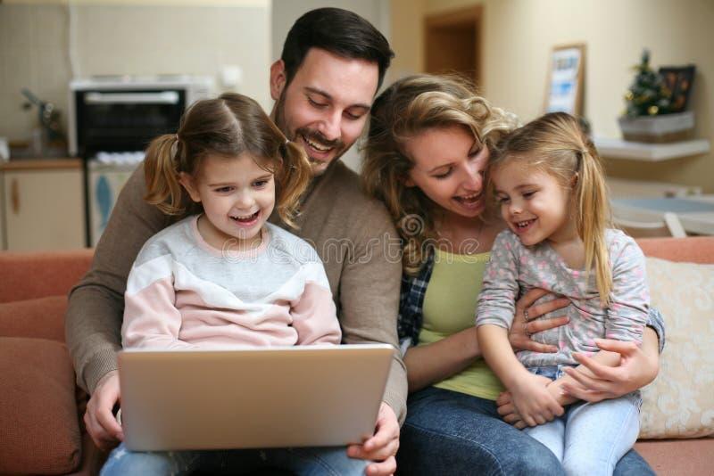 Família feliz que passa o tempo em casa e que olha no portátil Fá fotografia de stock