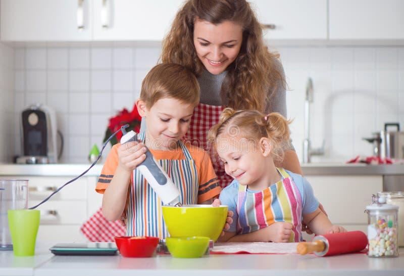 Família feliz que prepara cookies para a Noite de Natal fotografia de stock