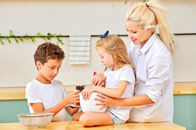 Família feliz que prepara a pastelaria na cozinha junto fotos de stock