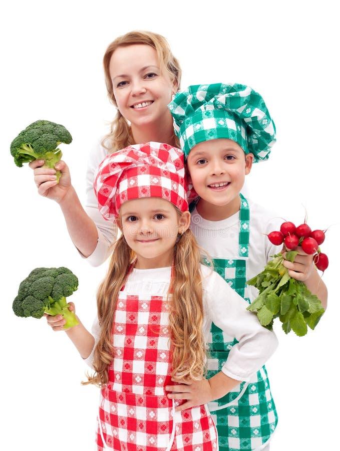 Família feliz que prepara a refeição de vegetais saudável fotos de stock royalty free