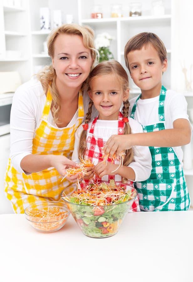 Família feliz que prepara a salada fresca fotografia de stock