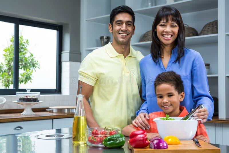 Família feliz que prepara a salada na cozinha foto de stock