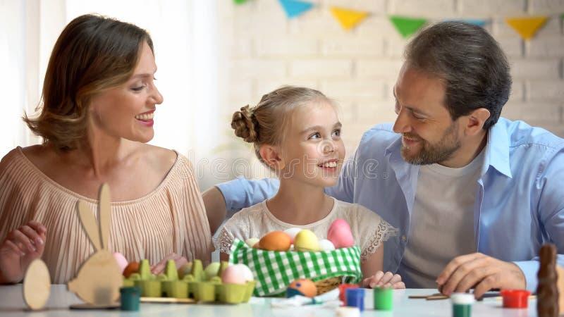 Família feliz que prepara-se para a celebração, os ovos e as pinturas da Páscoa na tabela, divertimento fotografia de stock royalty free