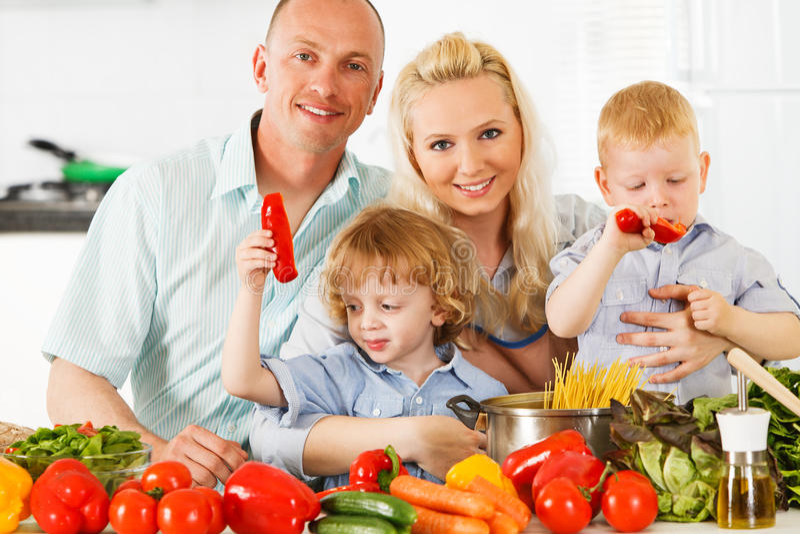 Família feliz que prepara um jantar saudável em casa. fotografia de stock royalty free