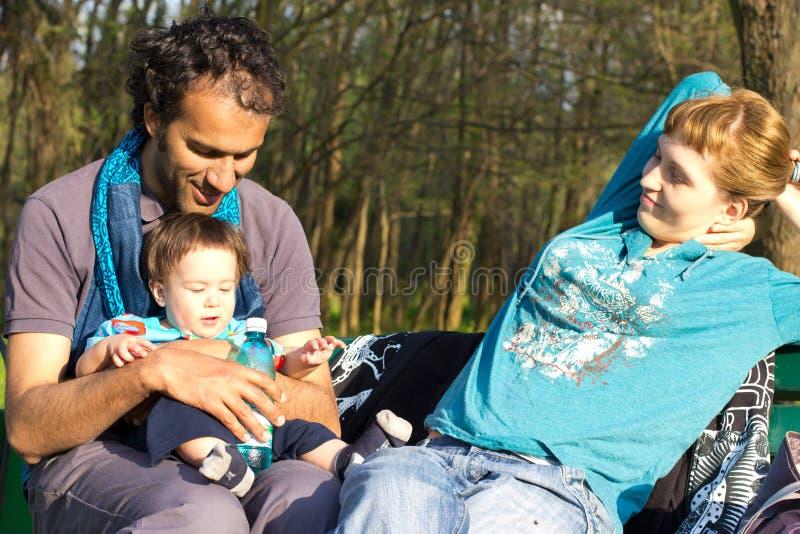 Família feliz que relaxa no parque fotografia de stock royalty free