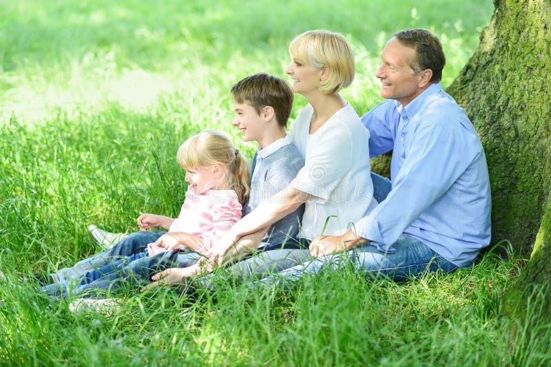 Família feliz que relaxa no parque imagens de stock royalty free