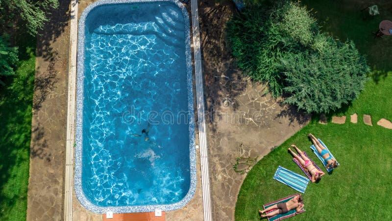A família feliz que relaxam pela piscina, a ideia aérea do zangão de cima dos pais e as crianças têm o divertimento em férias, fi foto de stock royalty free