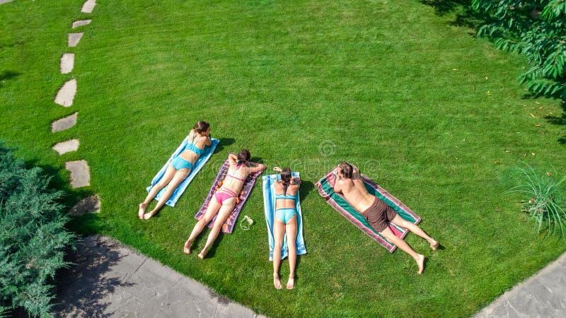 A família feliz que relaxam pela piscina, a ideia aérea do zangão de cima dos pais e as crianças têm o divertimento em férias, fi fotografia de stock