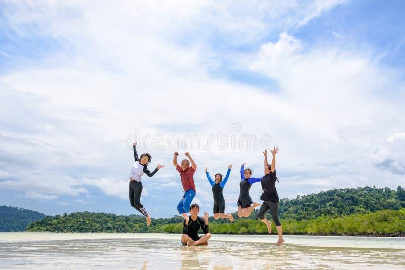 Família feliz que salta junto na praia, Tailândia fotografia de stock