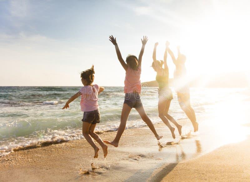 Família feliz que salta na praia no por do sol imagens de stock royalty free