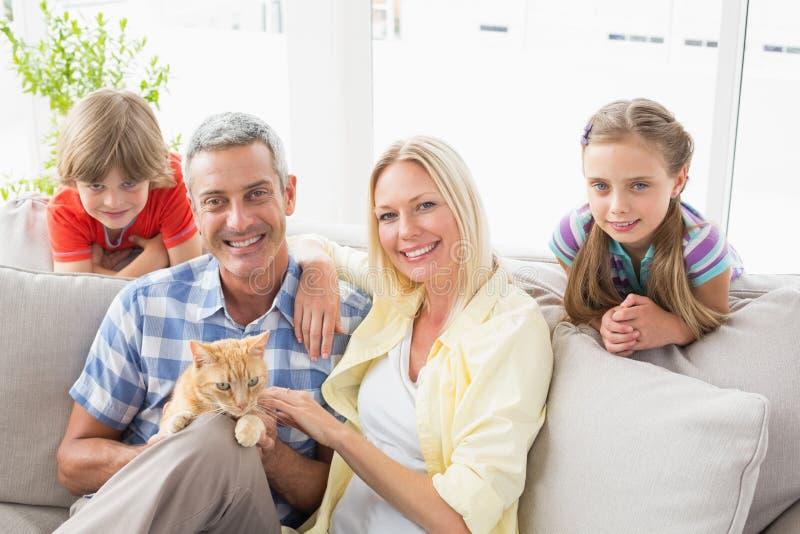 Família feliz que senta-se com o gato no sofá em casa imagem de stock royalty free