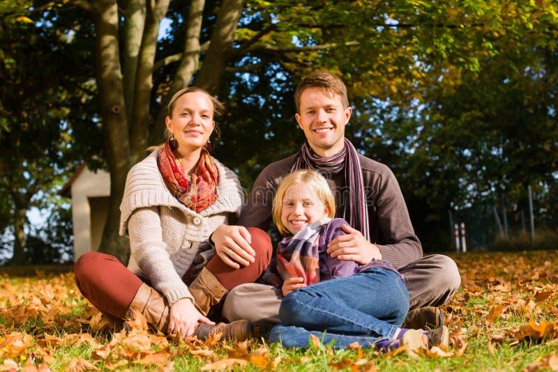 Família feliz que senta-se fora na grama no outono foto de stock royalty free