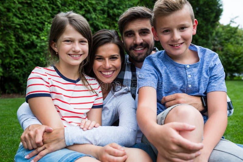 Família feliz que senta-se na grama no parque em um dia ensolarado imagem de stock