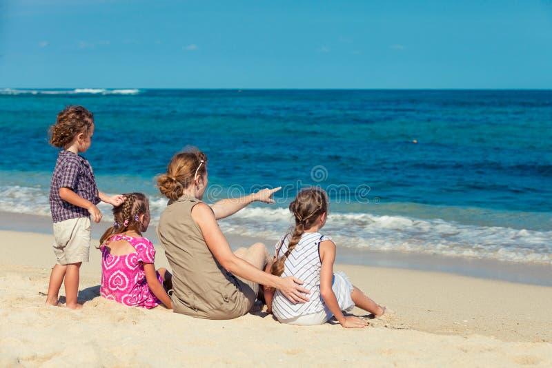 Família feliz que senta-se na praia fotografia de stock