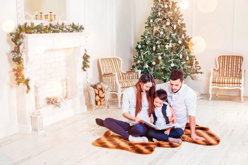 A família feliz que senta-se na sala de visitas que tem o livro de Natal, atrás da árvore decorada do Xmas, a luz dá uma atmosfer imagem de stock