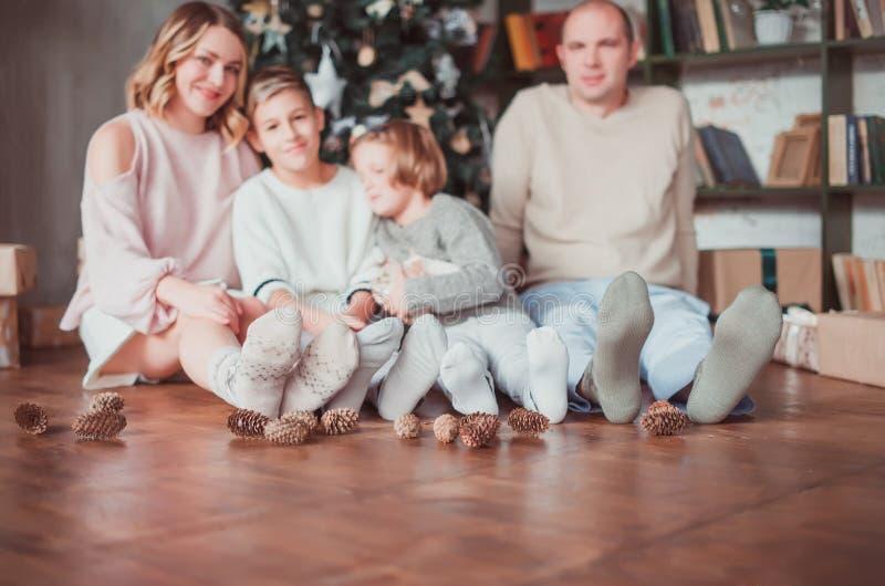 Família feliz que senta-se no assoalho de madeira na sala ao lado da árvore de Natal Riem No assoalho são os cones Cor morna imagens de stock royalty free