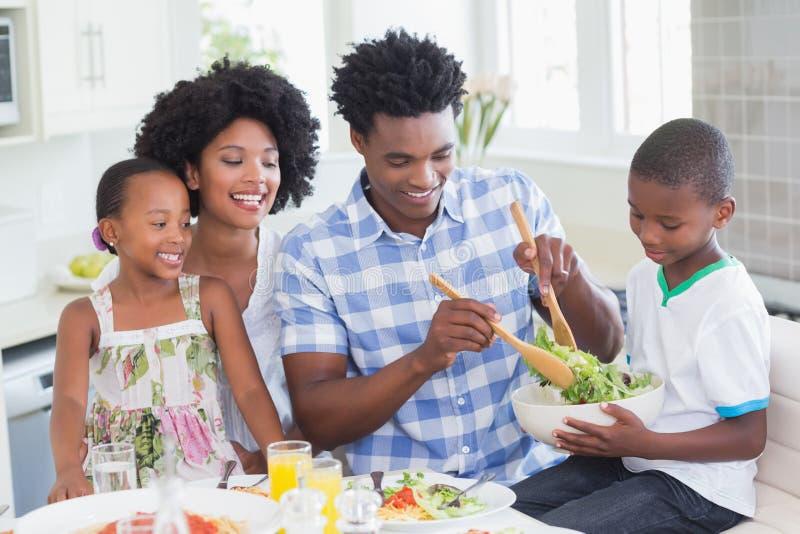 Família feliz que senta-se para baixo ao jantar junto fotografia de stock