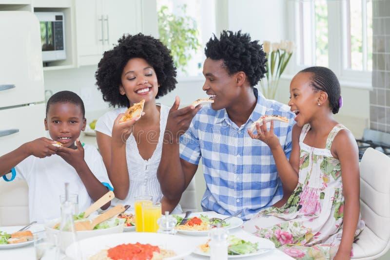Família feliz que senta-se para baixo ao jantar junto imagem de stock