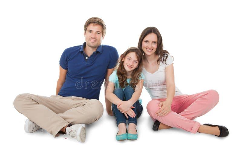 Família feliz que senta-se sobre o fundo branco fotos de stock