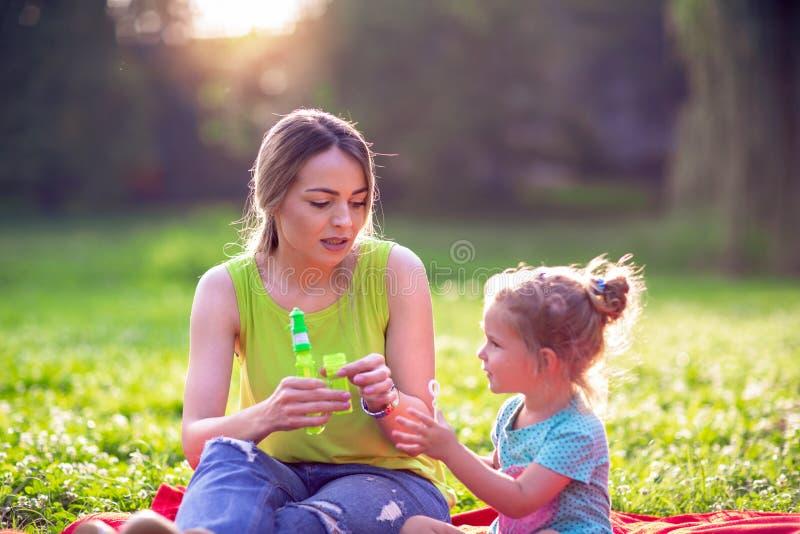 A família feliz que tem a criança do divertimento funde a espuma da sopa e faz bolhas com sua mãe na natureza fotos de stock royalty free