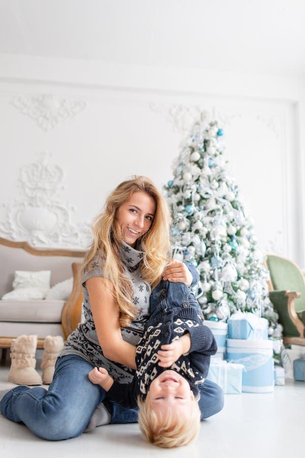 Família feliz que tem o divertimento em casa a mãe grávida dos jovens abraça seu filho pequeno Ano novo feliz Árvore de Natal dec imagem de stock royalty free
