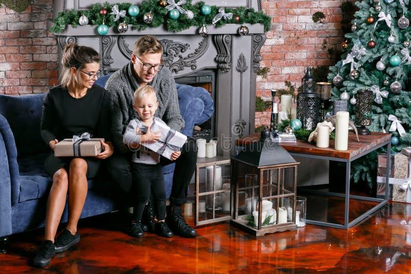 Família feliz que tem o divertimento em casa Manhã de Natal na sala do sótão com parede de tijolo Pais novos com filho pequeno pa fotografia de stock royalty free
