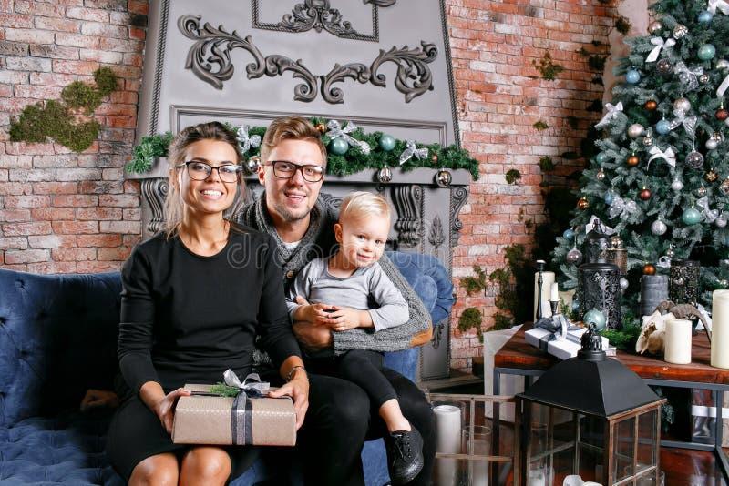 Família feliz que tem o divertimento em casa Na sala do sótão com parede de tijolo Pais novos com filho pequeno Pai, mãe e seu foto de stock