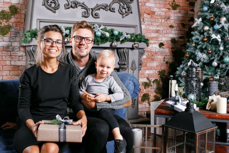 Família feliz que tem o divertimento em casa Na sala do sótão com parede de tijolo Pais novos com filho pequeno Pai, mãe e seu fotografia de stock
