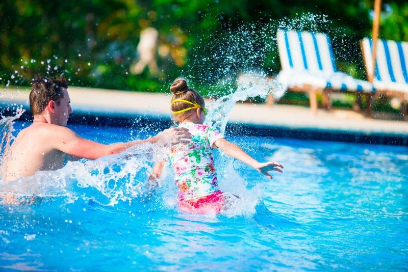 Família feliz que tem o divertimento junto na piscina do ar livre fotografia de stock royalty free