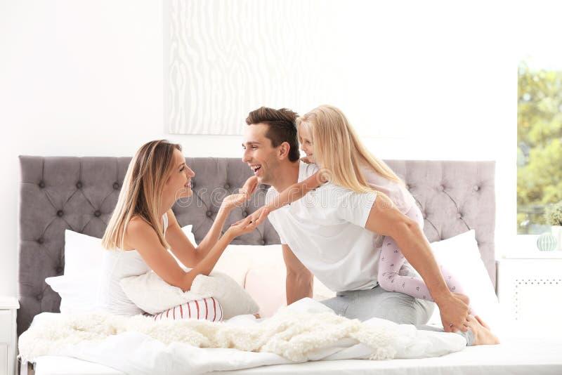 Família feliz que tem o divertimento na cama com descansos fotos de stock