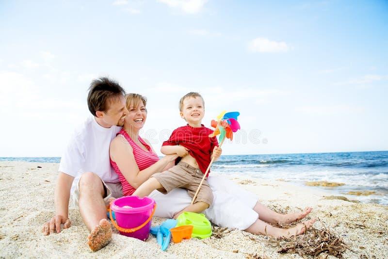 Família feliz que tem o divertimento na praia. imagem de stock
