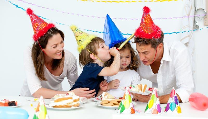 Família feliz que tem o fn ao comer o bolo de aniversário foto de stock