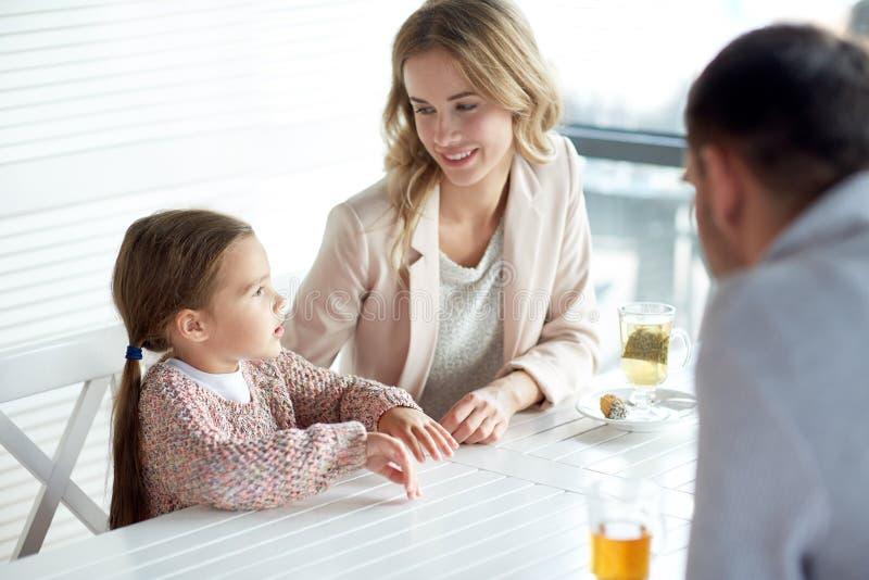 Família feliz que tem o jantar no restaurante ou no café foto de stock