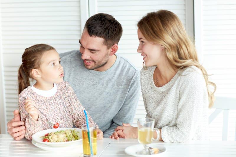 Família feliz que tem o jantar no restaurante ou no café fotografia de stock