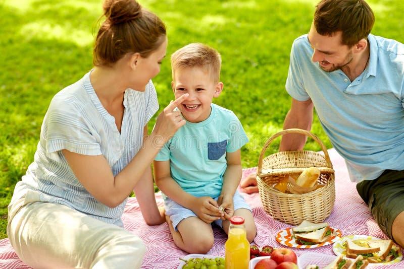 Família feliz que tem o piquenique no parque do verão foto de stock royalty free