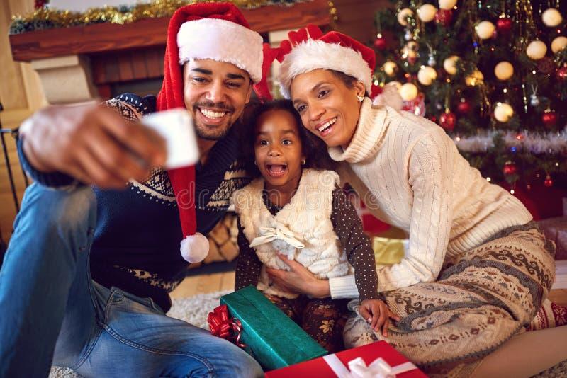 Família feliz que toma o autorretrato com o smartphone durante Christm fotografia de stock