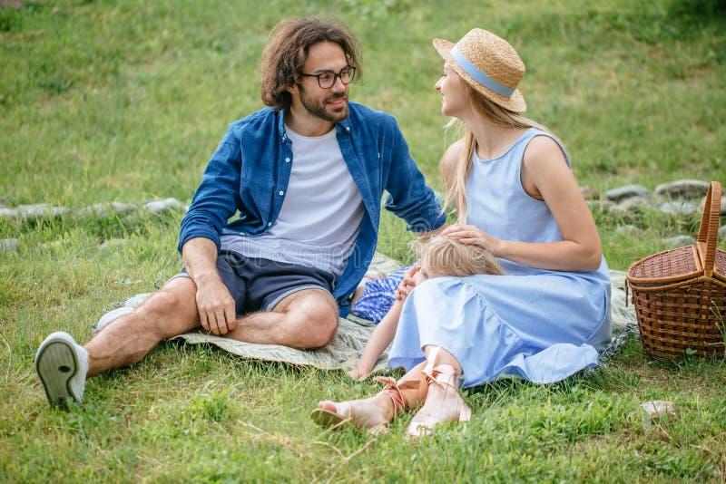 Família feliz que toma parte num piquenique fora com sua filha bonito, roupa azul, mulher no chapéu fotografia de stock royalty free