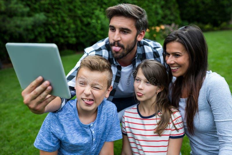 Família feliz que toma um selfie da tabuleta digital no parque fotos de stock
